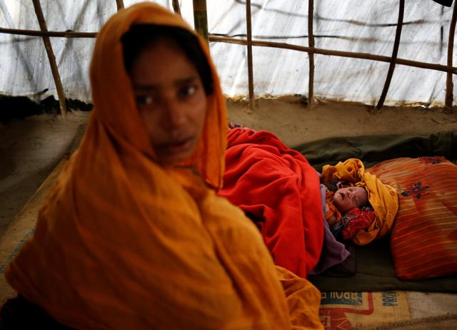 Noor Begum, 26, sits next to her one-day-old daughter Sumaiya as she poses for a photograph inside their shelter in Balukhali unregistered refugee camp in Cox's Bazar, Bangladesh, February 8, 2017. REUTERS/Mohammad Ponir Hossain