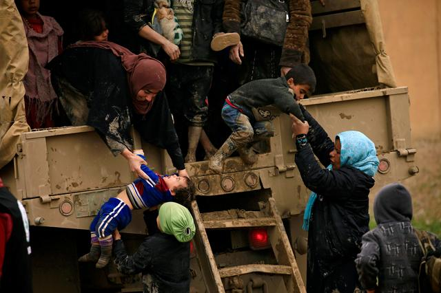 Displaced Iraqi women who fled their homes during a battle between Iraqi forces and Islamic State militants, try to get out of a vehicle with their children at a checkpoint, to be transfer to Hammam al-Alil camp, in Mosul. REUTERS/Thaier Al-Sudani