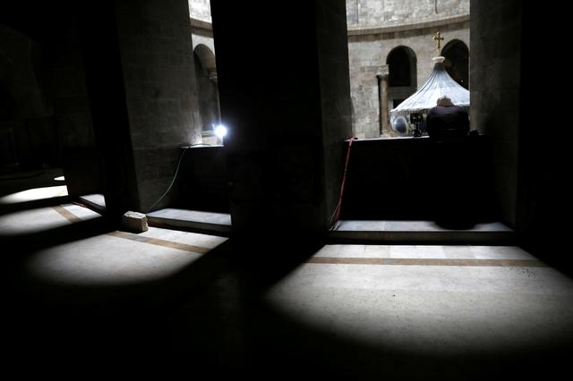 A priest looks down towards the newly restored Edicule, the ancient structure housing the tomb, which according to Christian belief is where Jesus's body was anointed and buried, at the Church of the Holy Sepulchre in Jerusalem's Old City March 20, 2017. REUTERS/Ronen Zvulun