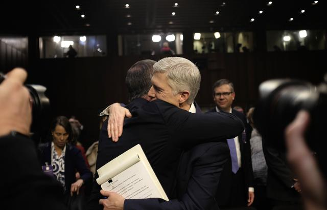 U.S. Supreme Court nominee judge Neil Gorsuch (R) is embraced by a supporter after delivering his opening statement at his Senate Judiciary Committee confirmation hearing on Capitol Hill in Washington, U.S., March 20, 2017. REUTERS/James Lawler Duggan