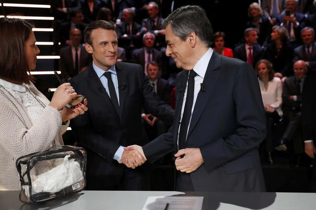 Candidates for the 2017 presidential election Francois Fillon (R), former French Prime Minister, member of the Republicans and candidate of the French centre-right and Emmanuel Macron, head of the political movement En Marche !, or Onwards !, shake hands before a debate organised by French private TV channel TF1 in Aubervilliers, outside Paris, France, March 20, 2017. REUTERS/Patrick Kovarik/Pool
