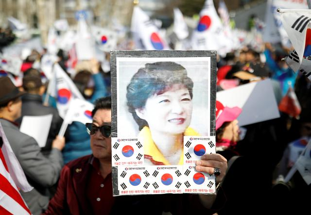 A supporter of South Korea's ousted leader Park Geun-hye holds up Park's portrait during a rally in front of a prosecutor's office in Seoul, South Korea, March 21, 2017.  REUTERS/Kim Hong-Ji