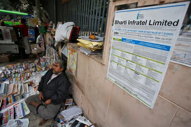 An advertisement for Bharti Infratel Limited's initial public offering (IPO) is seen posted on a wall as a roadside vendor selling magazines and newspapers waits for customers in New Delhi December 12, 2012.   REUTERS/Adnan Abidi/Files