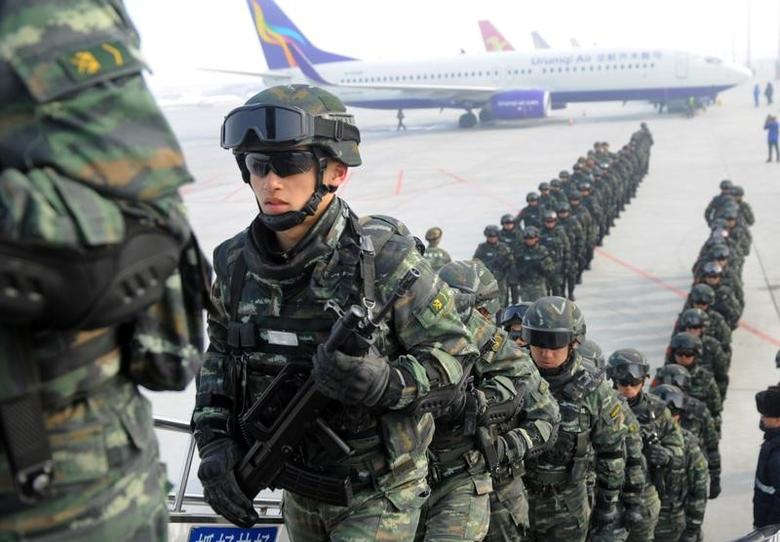 Paramilitary policemen board a plane as they head for an anti-terrorism oath-taking rally in Kashgar, from Urumqi, Xinjiang Uighur Autonomous Region, China, February 27, 2017. REUTERS/Stringer