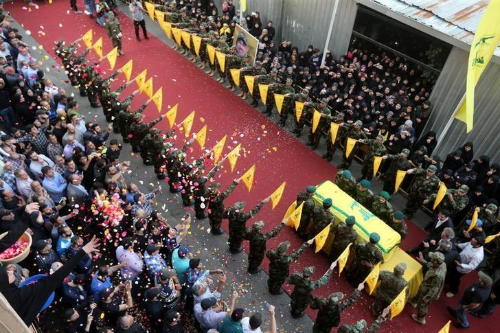 People toss rose petals as Hezbollah members stand near the coffin of top Hezbollah commander Mustafa Badreddine, who was killed in an attack in Syria, during his funeral in Beirut's southern suburbs, Lebanon, May 13, 2016. REUTERS/Hasan Shaaban