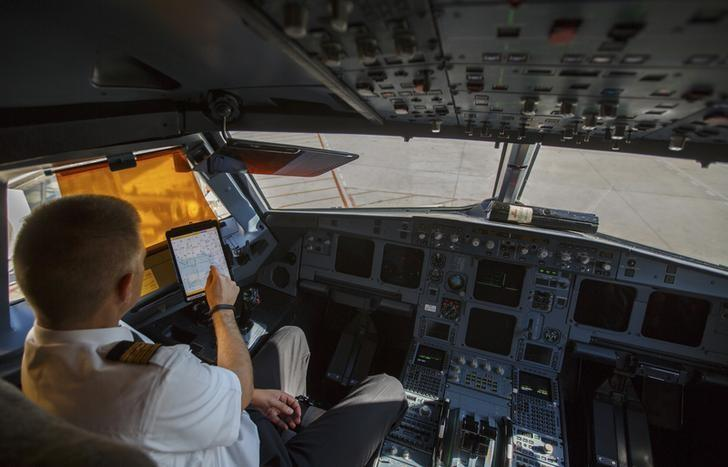 An Iberia Airlines pilot touches the screen of an iPad during a demonstration inside a cockpit of a passenger plane at Terminal 4 of Madrid's Adolfo Suarez Barajas airport November 6, 2014. Iberia is the first Spanish airline to use this electronic device which will replace the traditional books and papers that pilots use during flights. REUTERS/Sergio Perez  (SPAIN - Tags: TRANSPORT)