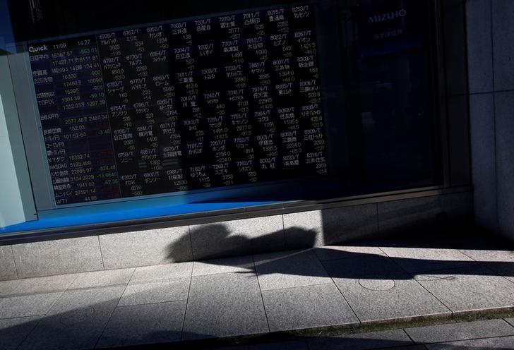 A pedestrian casts a shadow in front of an electronic stock quotation board outside a brokerage in Tokyo, Japan, November 9, 2016. REUTERS/Issei Kato/File Photo