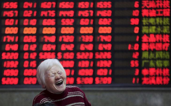 An investor reacts in front of an electronic board showing stock information at a brokerage house in Shanghai, China, March 7, 2016. REUTERS/Aly Song