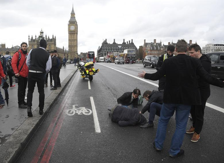 An injured person is assisted after an incident on Westminster Bridge in London, Britain. REUTERS/Toby Melville