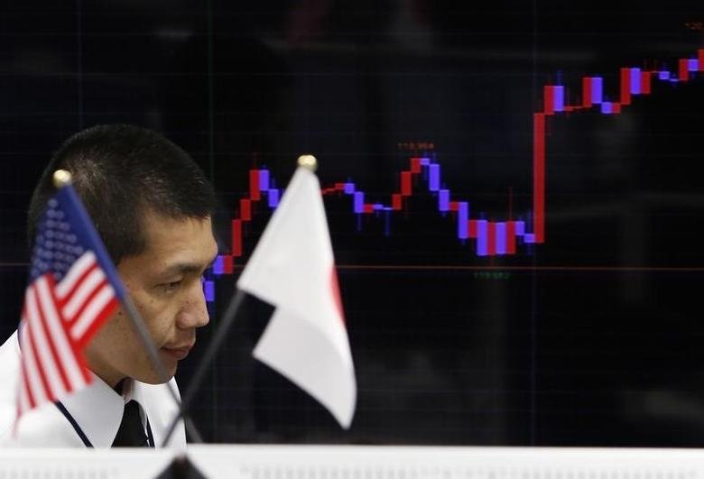 资料图片:2015年3月,在东京一家外汇交易公司内,一名雇员经过日美两国国旗和显示日元兑美元走势的屏幕。REUTERS/Yuya Shino