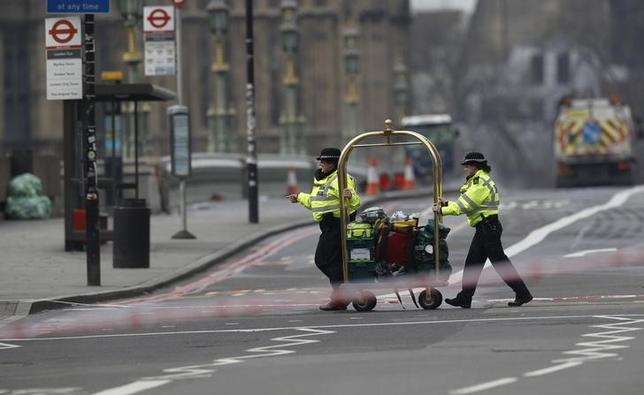 Police officers push medical equipment on a trolley accross Parliament Square the morning after an attack, in London Britain, March 23, 2017.  REUTERS/Darren Staples