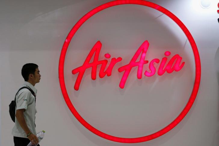 FILE PHOTO -  A man walks past the logo of AirAsia at Don Muang International Airport in Bangkok, Thailand, June 14, 2016.  REUTERS/Chaiwat Subprasom/File Photo