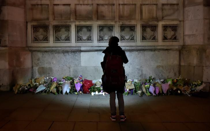 A woman looks at floral tributes laid in Westminster the day after a attack in London, Britain, March 23, 2017. REUTERS/Hannah McKay
