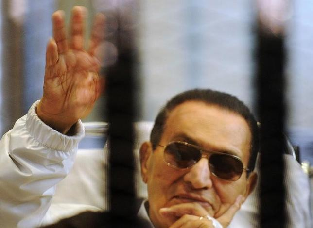 FILE PHOTO - Former Egyptian President Hosni Mubarak waves to his supporters inside a cage in a courtroom at the police academy in Cairo April 13, 2013. REUTERS/Stringer/File Photo