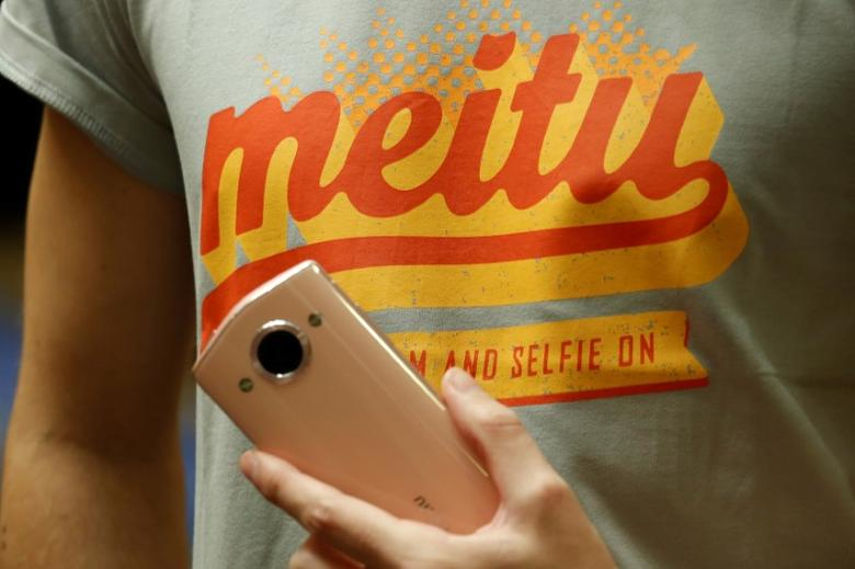 A model poses with a Meitu smartphone during Meitu IPO news conference in Hong Kong, China December 2, 2016.  REUTERS/Bobby Yip/Files