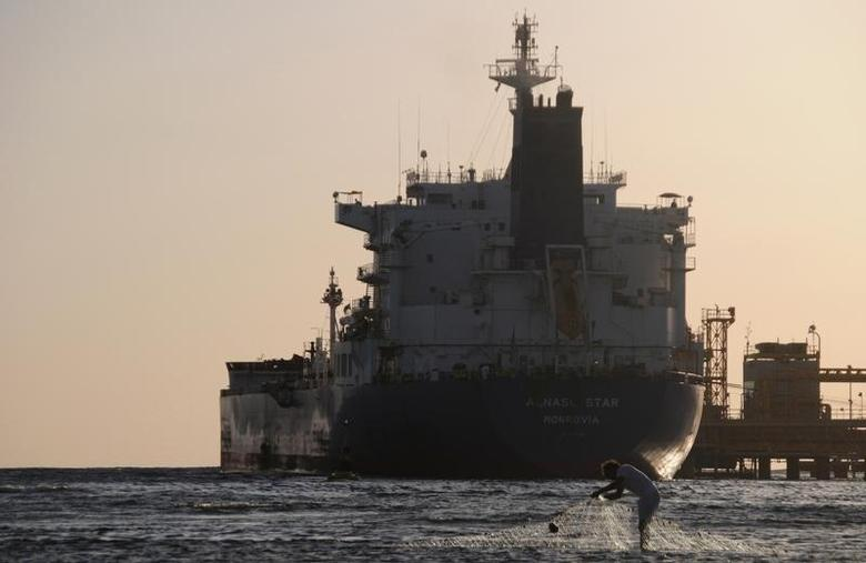 A fisherman pulls in his net as an oil tanker is seen at the port in the northwestern city of Duba April 20, 2013. Picture taken April 20. REUTERS/Mohamed Al Hwaity