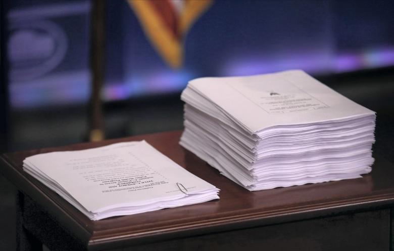 FILE PHOTO: A copy of Obamacare repeal and replace recommendations (L) produced by Republicans in the U.S. House of Representatives sit next to a copy of the Affordable Care Act known as Obamacare as U.S. Health and Human Services Secretary Tom Price addresses the daily press briefing at the White House in Washington, U.S. March 7, 2017.   REUTERS/Carlos Barria