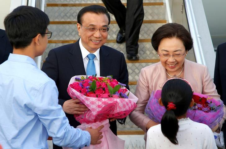 Chinese Premier Li Keqiang and his wife Cheng Hong reacts as they are handed flowers after arriving in Auckland, New Zealand, March 27, 2017.      REUTERS/Nigel Marple