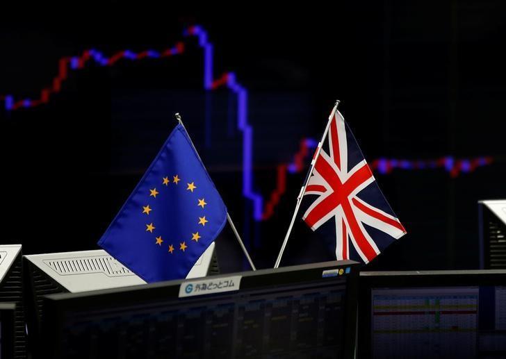 资料图片:2016年6月,东京一家外汇交易公司内,显示日元兑美元汇率的屏幕前悬挂着欧盟和英国国旗。REUTERS/Toru Hanai