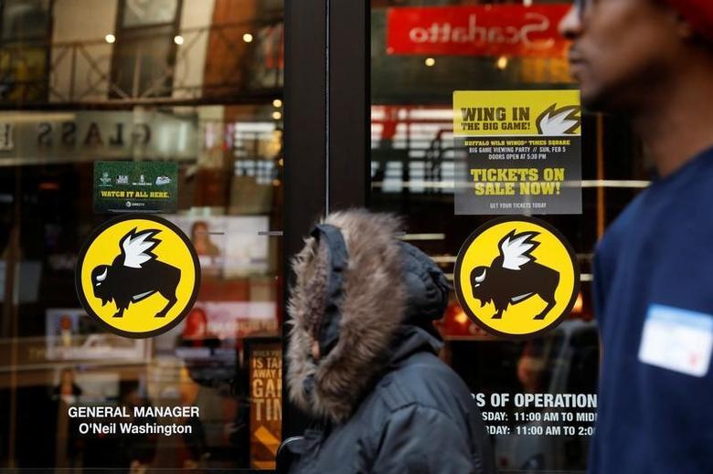 A pedestrian walks past a Buffalo Wild Wings restaurant in New York, U.S., February 6, 2017.  REUTERS/Lucas Jackson