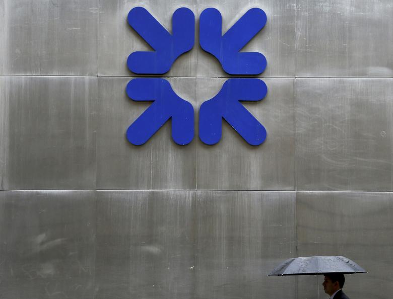 FILE PHOTO - A man shelters under an umbrella as he walks past a branch of the Royal Bank of Scotland in London, Britain, September 17, 2013.    REUTERS/Stefan Wermuth/File Photo