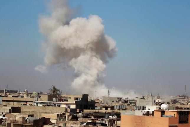 3月27日、米国防総省は、イラク北部モスルでの過激派組織「イスラム国」(IS)を標的とする作戦中に、米国主導の有志連合軍による空爆で多数の民間人が犠牲になった可能性があるとの非難を前に、交戦方針を変更する意向はないと強調した。写真は25日、イラク・イスラム国両軍の衝突で白煙をあげ炎上しているイラク・モスル(2017年 ロイター/Khalid al Mousily)