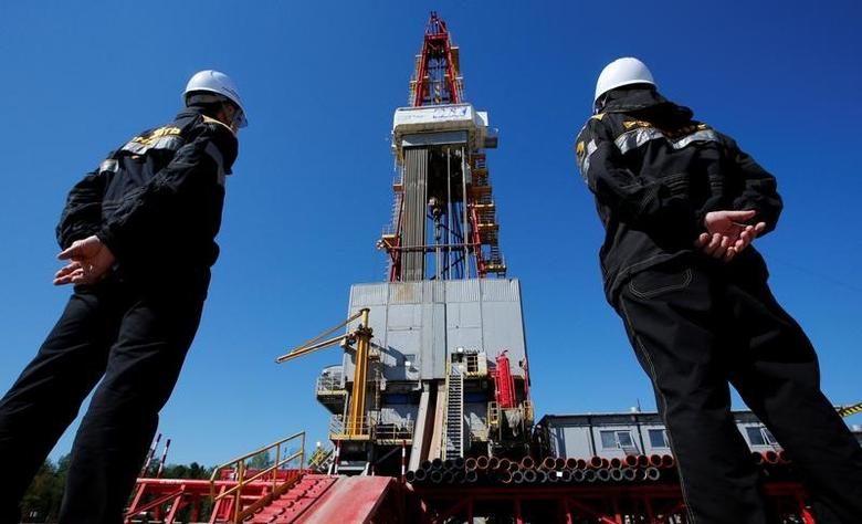 Workers look at a drilling rig at a well pad of the Rosneft owned Prirazlomnoye oil field outside Nefteyugansk, Russia, August 4, 2016.  REUTERS/Sergei Karpukhin/Files