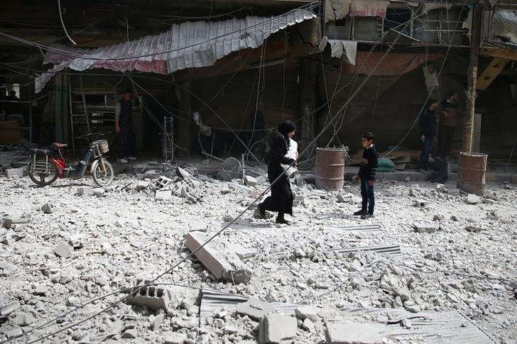 People walk at a site hit by an airstrike in the rebel held besieged Douma neighborhood of Damascus, Syria March 27, 2017. REUTERS/Bassam Khabieh