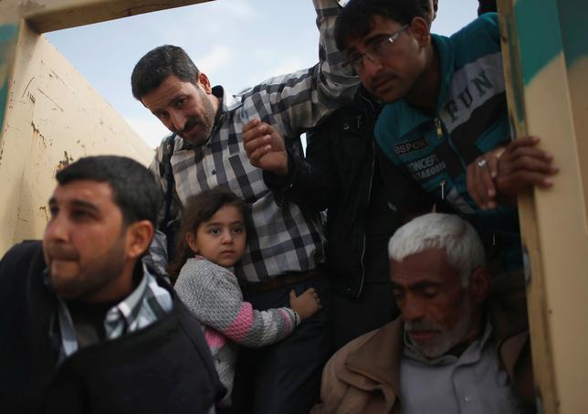3月28日、イラク北部モスルでの過激派組織「イスラム国」(IS)を標的とする作戦中、米軍主導の有志連合の空爆で多数の民間人が犠牲になったとされる問題について、米軍のタウンゼンド中将は、有志連合側に責任の一端があったことを認めた。写真はイラク北部のモスル南部で、家を追われ避難する民間人たち(2017年 ロイター/Suhaib Salem)