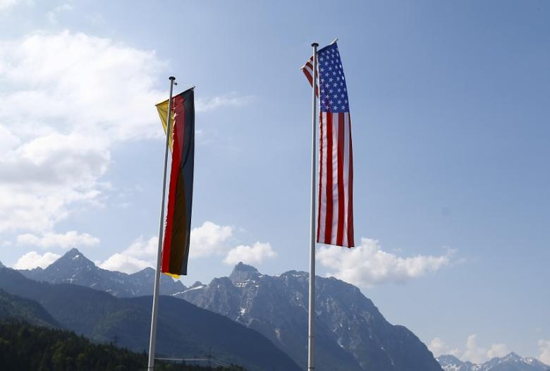 German and U.S. flags flutter above the Karwendel mountains in the Bavarian village of Kruen , southern Germany, June 6, 2015. The Group of Seven (G7) two-day summit, being held at Elmau palace in Bavaria, begins on Sunday.  REUTERS/Dominic Ebenbichler
