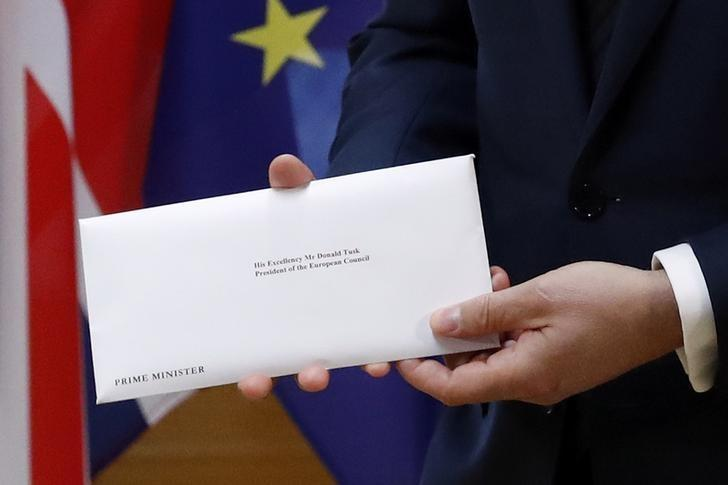 A detail shows EU Council President Donald Tusk who holds British Prime Minister Theresa May's Brexit letter which was delivered by Britain's permanent representative to the European Union Tim Barrow (not pictured) that gives notice of the UK's intention to leave the bloc under Article 50 of the EU's Lisbon Treaty in Brussels, Belgium, March 29, 2017.  REUTERS/Yves Herman