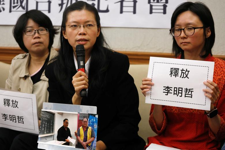 Li Ching-yu (C), holds photos of her husband, Taiwanese human rights activist Li Ming-che, detained in China, during a news conference in Taipei, Taiwan March 29, 2017. REUTERS/Tyrone Siu