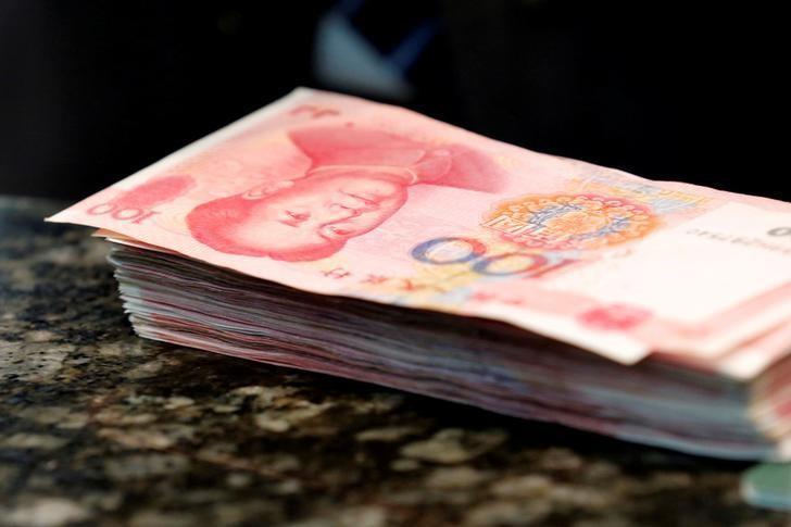 2016年3月30日,中国北京,一家商业银行支行柜台上的一摞人民币。REUTERS/Kim Kyung-Hoon
