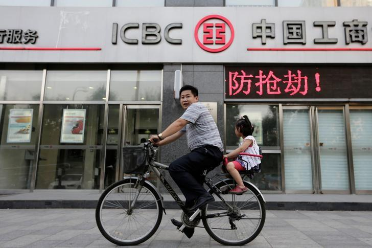 FILE PHOTO: A man and his daughter ride a bicycle past a branch of the Industrial and Commercial Bank of China Ltd (ICBC) in Beijing June 26, 2013.   REUTERS/Jason Lee/File Photo