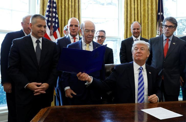 U.S. President Donald Trump smiles after announcing a permit for TransCanada Corp's Keystone XL oil pipeline while TransCanada Chief Executive Officer Russell Girling (L), U.S. Commerce Secretary Wilbur Ross (C) and U.S. Energy Secretary Rick Perry (R) stand beside him in the Oval Office of the White House in Washington, U.S., March 24, 2017. REUTERS/Kevin Lamarque