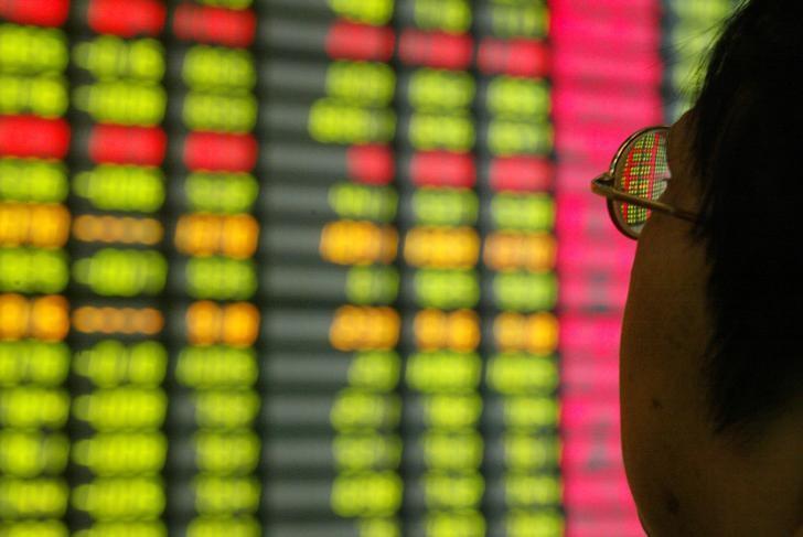 资料图片:2003年11月,上海一家券商营业部内的投资者盯着屏幕上的股票信息。REUTERS/Claro Cortes IV