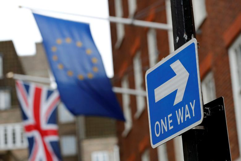 FILE PHOTO: A traffic sign is seen in front of European and Union flags in London, Britain, March 20, 2017. REUTERS/Stefan Wermuth/File Photo