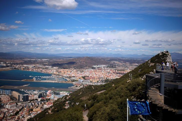 A general view shows the Spanish city of La Linea de la Concepcion (rear) and the tarmac of the Gibraltar International Airport (bottom L) while tourists stand on the top of the Rock (R) next to the European Union flag, in the British overseas territory of Gibraltar, September 14, 2016. REUTERS/Jon Nazca/Files