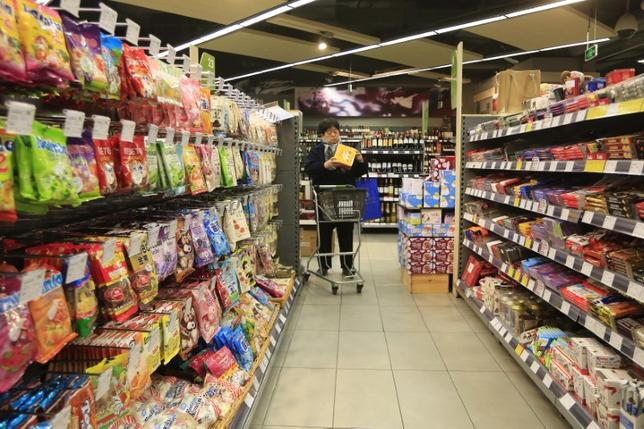 A customer selects products at a supermarket in Shanghai, February 10, 2015. REUTERS/Aly Song