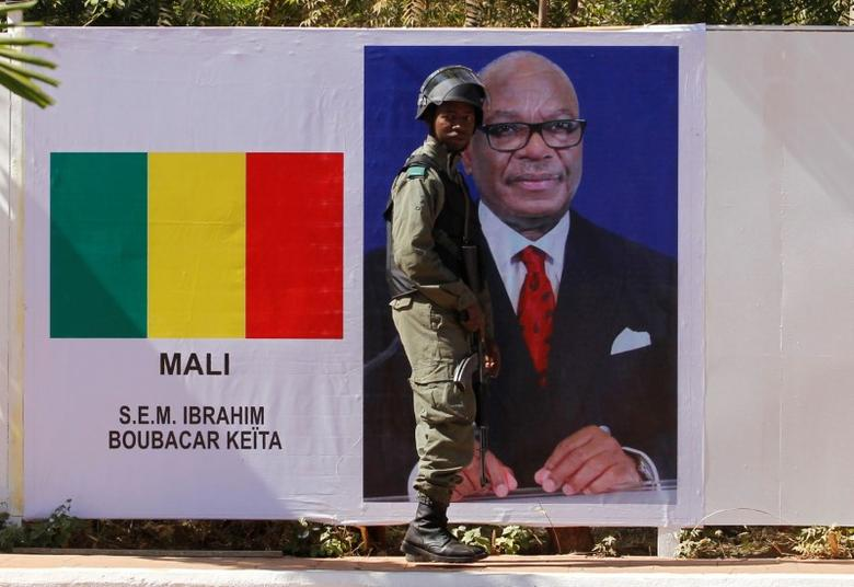 A Malian soldier stands guard next to Malian President Ibrahim Boubacar Keita's portrait at the international conference center of Bamako ahead of France-Africa summit in Bamako, Mali, January 12, 2017. REUTERS/ Luc Gnago