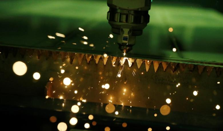 FILE PHOTO: A laser cutter produces sparks as it cuts a sheet of steel into components at a factory near Stafford, central England December 15, 2016. REUTERS/Phil Noble