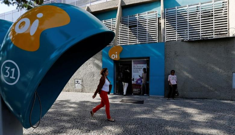 People walk in front of the headquarters of the Brazil's largest fixed-line telecoms group Oi, in Rio de Janeiro, Brazil, June 22, 2016. REUTERS/Sergio Moraes
