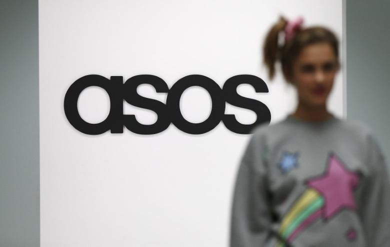 FILE PHOTO: A model walks on an in-house catwalk at the ASOS headquarters in London April 1, 2014. REUTERS/Suzanne Plunkett
