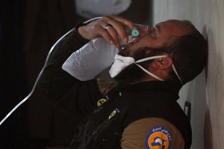 A civil defence member breathes through an oxygen mask, after what rescue workers described as a suspected gas attack in the town of Khan Sheikhoun in rebel-held Idlib, Syria. REUTERS/Ammar Abdullah