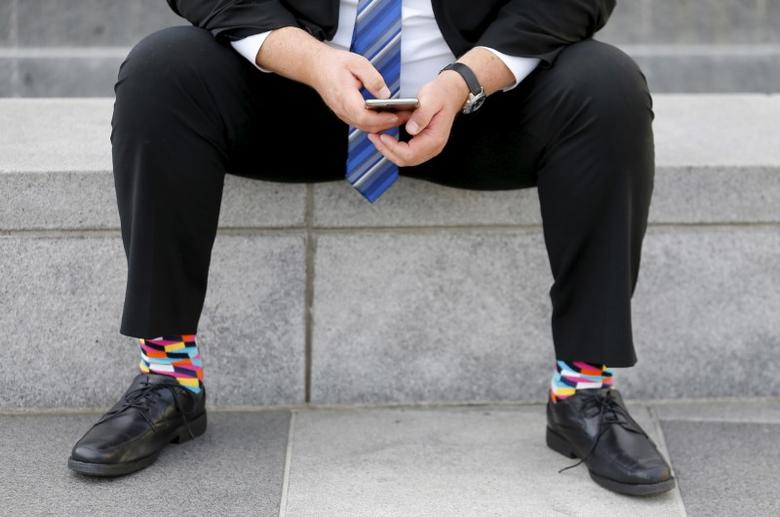FILE PHOTO: A businessman sits on a bench looking over his mobile phone in downtown San Francisco, California February 4, 2016.  REUTERS/Mike Blake