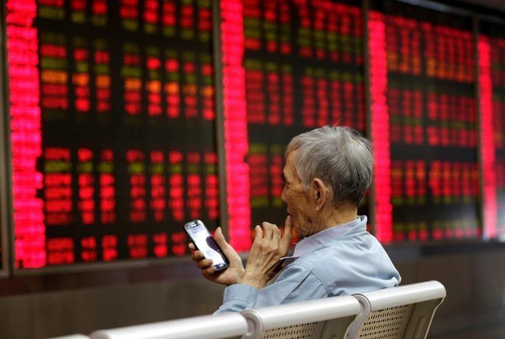资料图片:2016年6月,北京一家券商营业部内的股民在看手机上的股票信息。REUTERS/Jason Lee