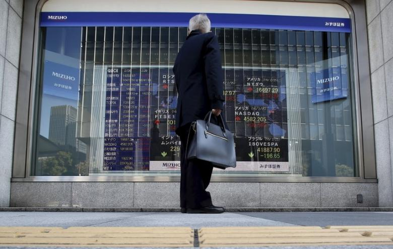 A pedestrian stands to look at an electronic board showing the stock market indices of various countries outside a brokerage in Tokyo, Japan, February 26, 2016. REUTERS/Yuya Shino