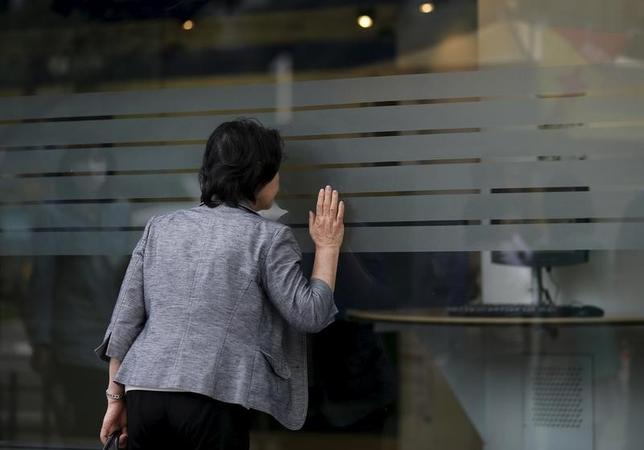 4月6日、東京株式市場で日経平均は、大幅反落。終値でも年初来安値を更新し、12月7日以来約4カ月ぶりの安値水準で引けた。写真は証券会社内を覗き込む通行人。2015年10月、都内で撮影(2017年 ロイター/Toru Hanai)