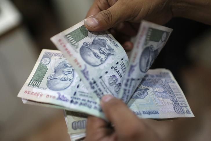 An employee counts rupee notes inside a private money exchange office in New Delhi July 5, 2013.  REUTERS/Adnan Abidi/File Photo