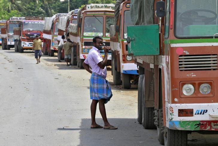 A truck driver brushes his teeth next to his parked truck while waiting to get his loads cleared to cross a checkpoint at the Commercial Taxes Department check post at Walayar in Palakkad district in Kerala, September 5, 2015.  REUTERS/Sivaram V/File Photo
